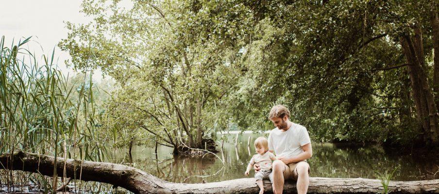 Ein Vater sitzt mit seiner Tochter auf einem Baumstamm im Wasser. Das Titelbild des Blogbeitrags